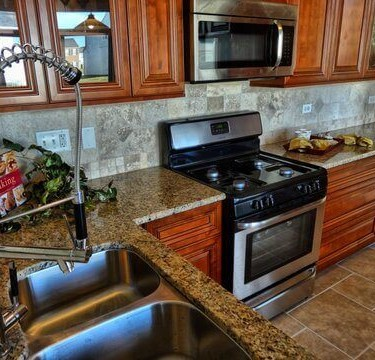 cherry wood cabinetry counters and sink installed by kitchen remodeling contractor