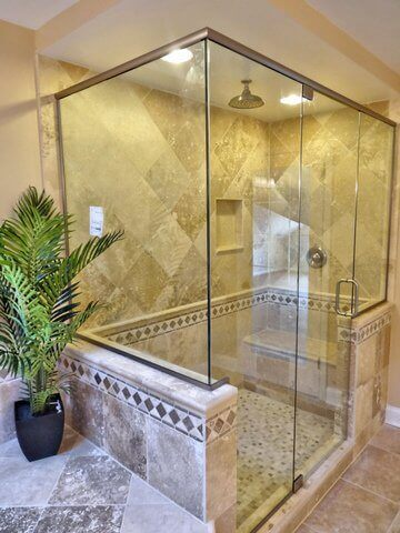 frameless glass installed in travertine shower with bench by bathroom remodeling contractor