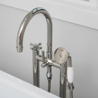 bathroom remodeling contractor shows close up of tub filler and body sprayer