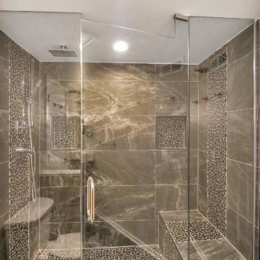 waterfall showerhead and frameless glass in custom shower