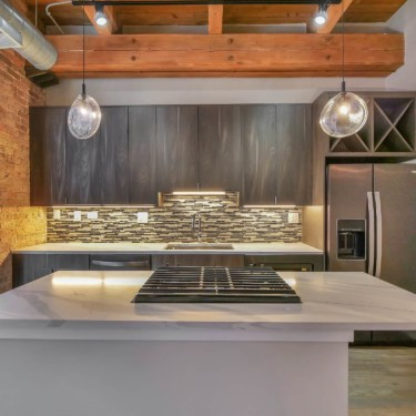 kitchen remodeling contractor showcases modern cabinets in chicago loft