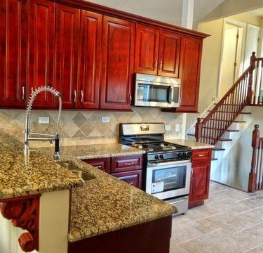 red wine cabinets and travertine backsplash installed by kitchen remodeling contractor