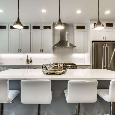 gray island and white stools by kitchen remodeling contractor